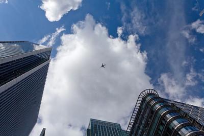 天空与飞机包围的摩天大楼