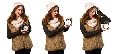 套装的女孩冬季衣服持有老式时钟