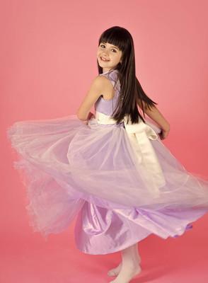 快乐的年轻女孩在紫罗兰色礼服