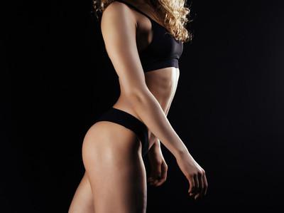年轻的女运动员,回来在黑暗的背景图片。在工作室里健身模特