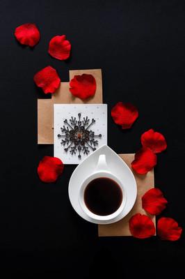 白色的咖啡在黑色的背景与玫瑰花瓣与复制空间, 平坦的铺设顶部视图。艺术潮流魅力浪漫风格