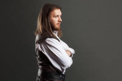 英俊男蒸汽朋克皮革背心。复古男人肖像在灰色的背景