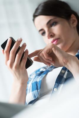 在移动电话上的女人发短信