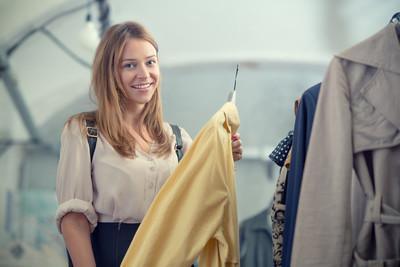 年轻的金发女人选择的衣服在商店
