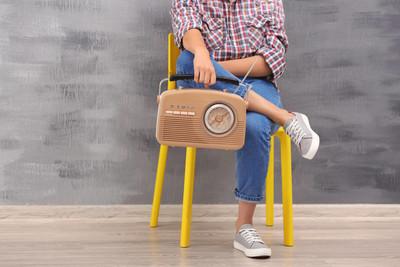 坐在椅子上在室内的复古收音机的年轻女子