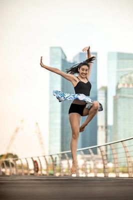 美丽的年轻女孩在城市跳舞, 与摩天大楼的背景