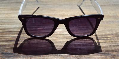 黑墨镜与紫罗兰色镜片上木桌特写