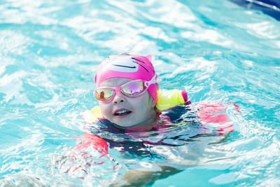 小女孩在游泳背心和游泳杯游泳在室外游泳池