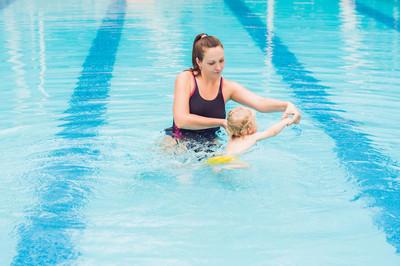年轻母亲教小儿子, 如何在白天游泳在游泳池