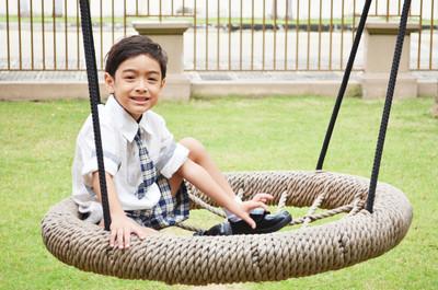 学生的男孩在学校玩秋千