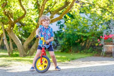 孩子男孩在花园里驾驶三轮车或自行车