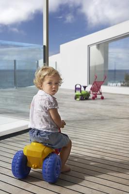 小男孩骑玩具三轮车