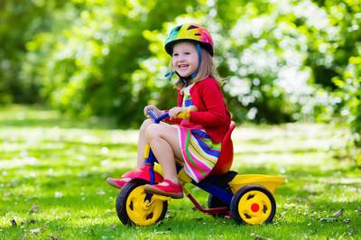 小女孩骑着三轮车